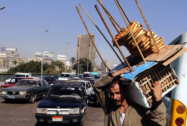An Egyptian bread vendor looks for buyers on a bridge over the Nile in Cairo last month.