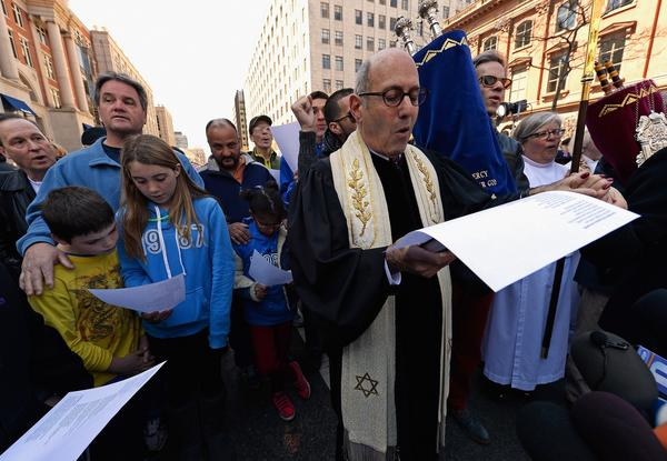 Rabbi Howard Berman of Central Reform Temple participates in an interfaith memorial service with members of six churches at a makeshift memorial for victims near the site of the Boston Marathon bombings at the intersection of Boylston Street and Berkley Street.