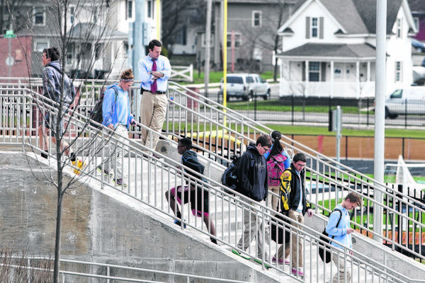 St. Joseph High School Assistant Principal Marty Harshman, leaning against the railing at the top of the stairs, watches as students leave the building after classes last Monday. Area school districts reported a huge spike in absences as many parents kept their children home amid safety concerns sparked last week by a threat against Elkhart and St. Joseph county schools.