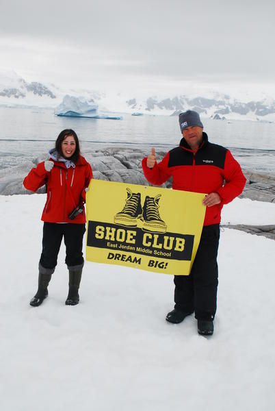 Shayna De Silva (left) and Robert Swan hold up the East Jordan Shoe Club banner in Antarctica.