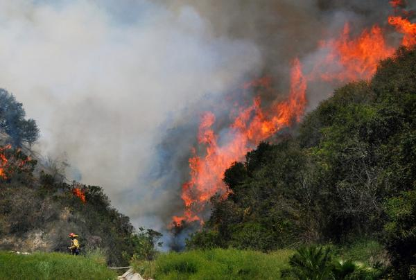A U.S. Forest Service firefighter, bottom left, turns to flee as flames roar up a mountainside in the early stages of a brush fire that started in the foothills of Monrovia.