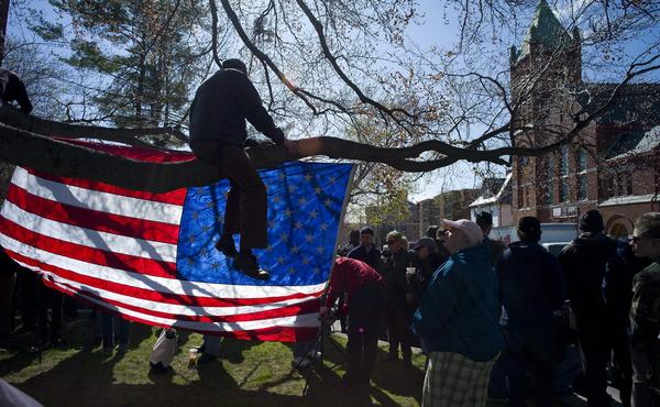Supporters hang an American Flag in a tree across the street from St. Joseph's Church in Medford, Mass., before the start of the funeral for bombing victim Krystle Campbell.