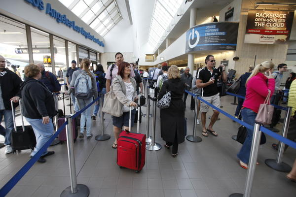 Passengers wait to go through security screening inside terminal one at Los Angeles International Airport Monday morning.
