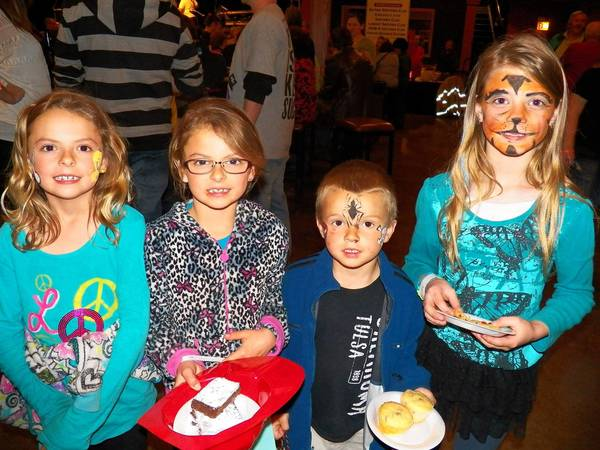 Four children showing off their face painting designs and enjoying goodies from the bake sale at last year's BIG Event for Sertoma Centre Inc.