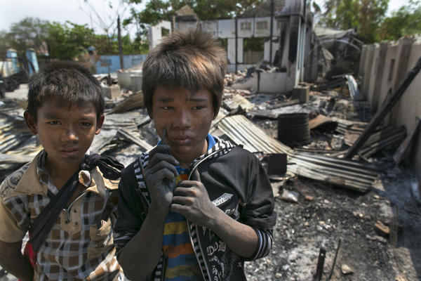 Two boys stand near their destroyed home April 5 in Meiktila, Myanmar. Recent sectarian violence between Buddhists and Muslims has left dozens dead, and Human Rights Watch said Monday that the attacks on Rohingya Muslims amount to crimes against humanity.