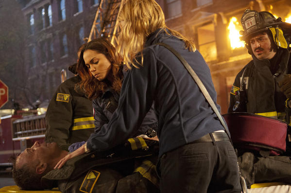 "David Eigenberg, lying down, Monica Raymund, Lauren German and Yuri Sardarov in a scene from ""Chicago Fire."""