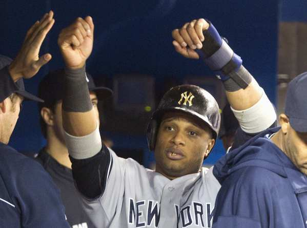 New York Yankees' Robinson Cano is congratulated in the dugout after scoring the Yankees third run on a bases loaded walk by Toronto Blue Jays pitcher Josh Johnson in the fifth inning of their game Sunday.