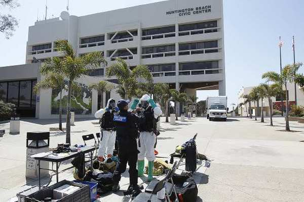 Members of the Huntington Beach hazardous materials team don hazmat suits before collecting a sample of a substance found in an envelope at the Huntington Beach City Hall on Monday. The building, with roughly 300 people, was evacuated.