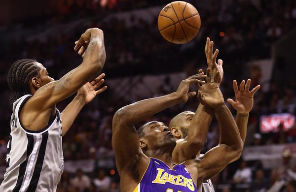 Lakers forward Metta World Peace battles Spurs forward Kawhi Leonard and power forward Tim Duncan (background) for a rebound in the first half Sunday afternoon.