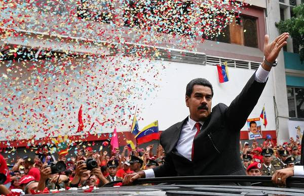 Nicolas Maduro waves to supporters before is swearing-in Friday as Venezuela's president.