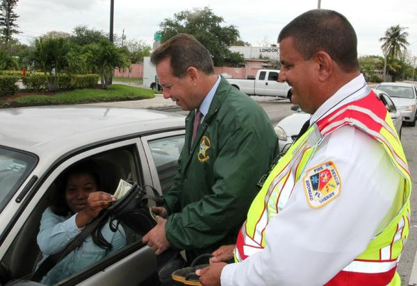 Broward Sheriff Scott Israel (center) and Fire Rescue Chief Tony Stravino (right) kick-off the week-long Fill The Boot fundraising drive to find a cure for Muscular Dystrophy