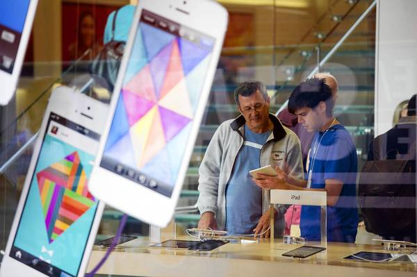 Apple might lower its guidance for the current quarter that ends in June. Above, a customer receives help from an employee at a store in San Francisco.