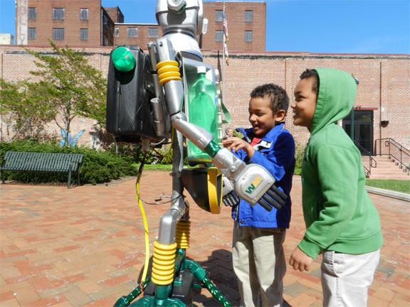 Isaac Brown, 4, of Hagerstown, right, and his twin brother Ellis, 4, play with Cycler the recycle robot Monday in University Plaza. The robot was part of an Earth Day celebration that involved local officials, Barbara Ingram School for the Arts, and Pangborn Elementary School students.