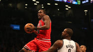 Bulls forward Luol Deng soars to the basket in front of Nets center Andray Blatche. (Nuccio DiNuzzo/Tribune photo)