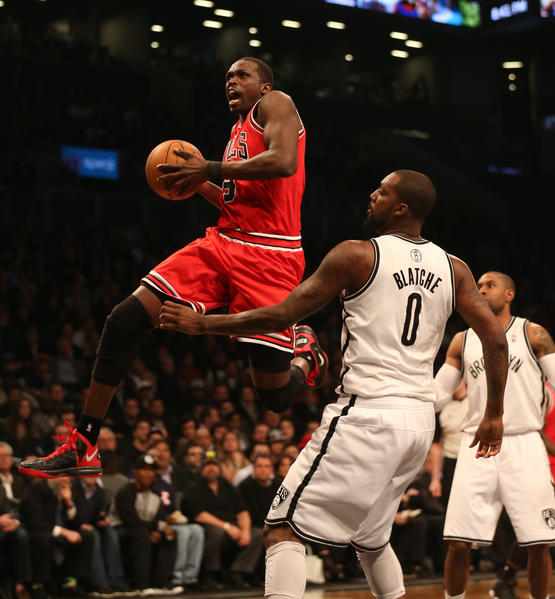 Bulls forward Luol Deng soars to the basket in front of Nets center Andray Blatche.
