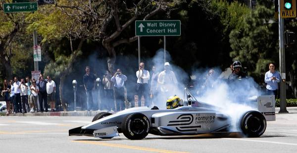 Lucas Di Grassi spins his wheels while demonstrating the new Formula E electric race car prototype on Hope Street in L.A. on Monday.