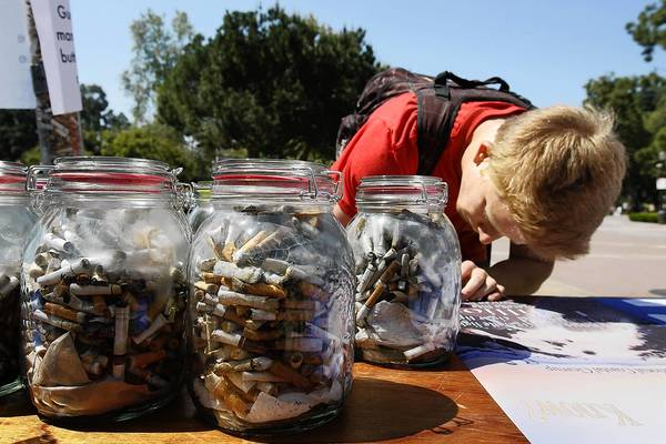 UCLA student Zak Baron, 20, tries to guess how many cigarette butts are in the cylinder at upper left. In the foreground are jars full of butts that had been collected in various locations on campus. On Monday, Earth Day, the Westwood campus became the first in the UC system to ban tobacco.