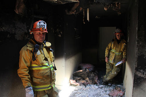 LAFD Capt. George James, left, and Capt. Charles Ruddell survey the charred apartment building.