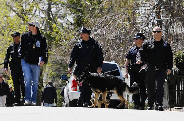 Authorities reinvestigate an area Monday in Watertown, Mass., where one of the Boston bombing suspects was caught last week. Obama administration critics wanted the suspect held as an enemy combatant.