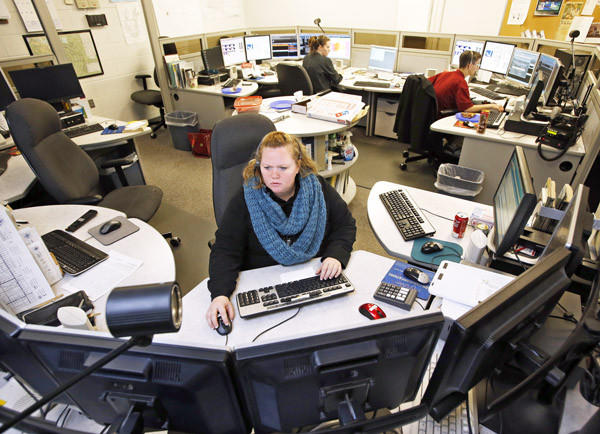 Christine Haggerty, center, works on a call as fellow dispatchers Cortney Erickson, back center, and Cory Erhardt, back right, work another call around midnight Friday in the dispatch center at the Brown County Courthouse.