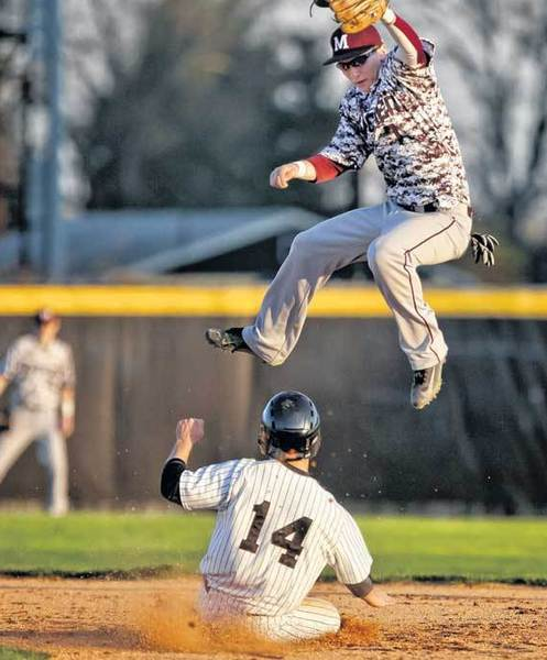 Penn's Christopher Como slides in safely after stealing second base as Mishawaka's Matt Carver leaps for a high throw during their game Monday at Penn.