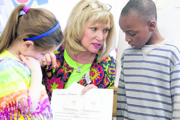 Sue Panzica, the South Bend Community School Corp. Teacher of the Year, helps kindergarten students Eva Wells, left, and Jayon Willis arrange numbers in an exercise Monday at Swanson Primary Center.