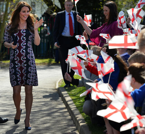 Britain's Catherine, Duchess of Cambridge (L) waves at children waving English flags as she arrives on her visit to The Willows Primary School, Wythenshawe, Manchester, northwest England on April 23, 2013 to launch a new school counselling programme. The duchess of Cambridge met staff and volunteers, teachers and parents at the school as she launched the programme, which is a partnership between the Royal Foundation, Comic Relief,  Place2Be and Action on Addiction.  AFP PHOTO / POOL / PAUL ELLISPAUL ELLIS/AFP/Getty Images ORG XMIT: