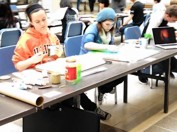 Sara Litzenberger and Elizabeth Koskiewicz, both seniors at Geneva High School, work on their paintings at the school's second Vision Walls event.