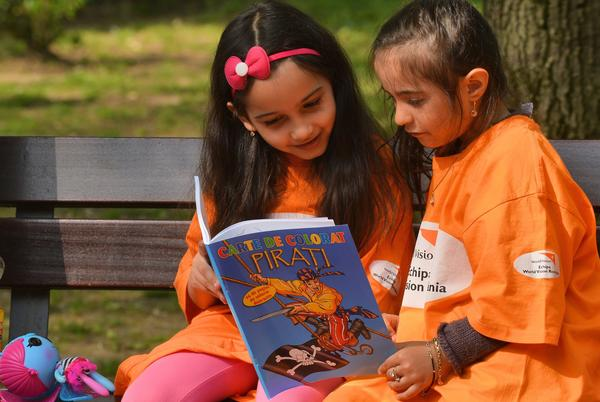 Children share a book on World Book Night (and Day) in Bucharest, Romania.
