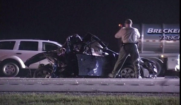 An investigator takes photos of a vehicle involved in a fatal crash on the Reagan Memorial Tollway Monday night.
