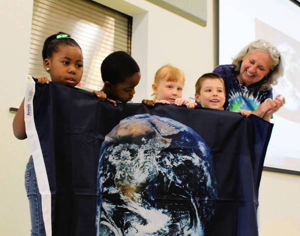 Conservation educator Kay McKeen awards an Earth Flag to pre-kindergarten students at the Ann Reid Early Childhood Center in Naperville.