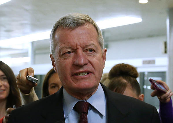 Sen. Max Baucus (D-Mont.) is trailed by reporters Tuesday on Capitol Hill in Washington. Baucus announced that he will not seek reelection in 2014.