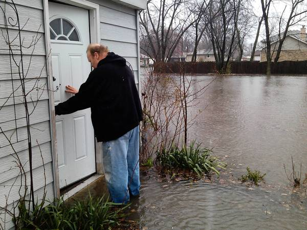 Timothy O'Brien, 56, walks into his flooded shed on April 18.