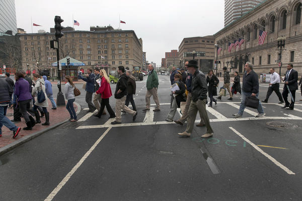 People cross Dartmouth Street en route to their businesses and homes along Boston's Boylston Street.
