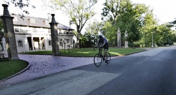 A bicyclist rides down Lake Road in front of this lakeside mansion in Lake Forest.