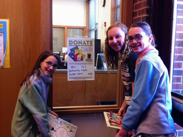 Mia Lucci, left, Lucy Economos and Brooke West, right, set up a book collection side at Roosevelt Middle School this week.