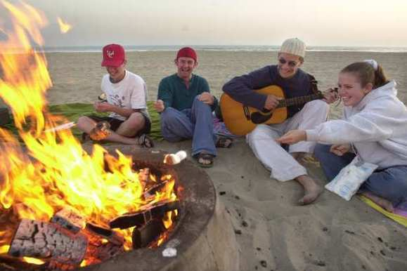 A group of friends gather by a fire ring in Newport Beach. Air regulators are considering a ban on the Southern California tradition.