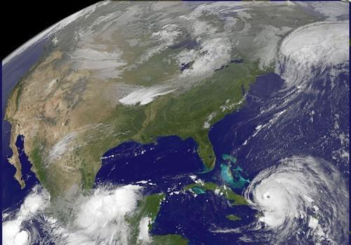 This image provided by NOAA taken at 7:10 a.m. EDT Sunday Sept. 7, 2008 shows Hurricane Ike in the lower left. Hurricane Ike roared across the low-lying Turks and Caicos Islands before dawn Sunday as people in the British territory sought refuge in boarded-up homes or shelters. The ferocious Category 4 storm dwarfed the tiny islands, packing 135-mph winds and 13 to 18 foot storm surge above normal tide levels. The storm is heading towards the Bahamas later Sunday morning and is forecast to hit Cuba Sunday evening according to the National Hurricane Center in Miami. (AP Photo/NOAA) ORG XMIT: NY110
