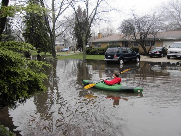Paul McAllester, 11, kayaks down his flooded street in Wilmette on Thursday morning.