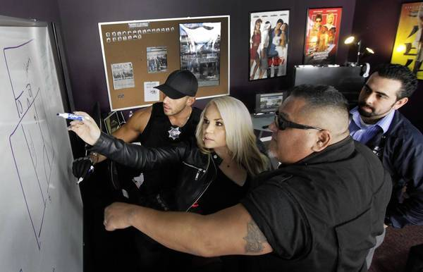 "Roman ""Bombero"" de la Torre, Monique Covarrubias, Roman Morales III, main characters of mun2's cable TV show about bounty hunters in LA, ""Fugitivos de la Ley"" and Gustavo Lopez, the show's script writer discussing the next location shoot in Pacoima."