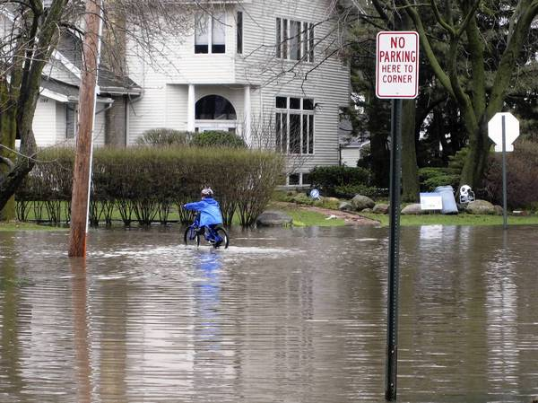A child bicycles through a completely submerged intersection at Ash Street and Glendale Avenue in Winnetka on April 18.