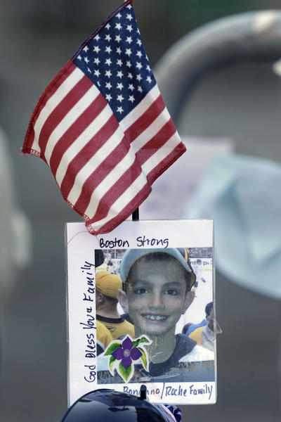 A photograph of bombing victim Martin Richard, 8, is attached to a barricade in Boston. The youngest victim in the bombing was buried Tuesday.