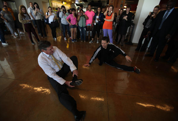 Cal State Chancellor Timothy White, left, tours Cal State Dominguez Hills in Carson. After the students danced in a flash mob for him, he took off his shoes and tried to emulate the break dancing moves of senior Michael Amaton, 32, of Hermosa Beach, to the delight of the other students.