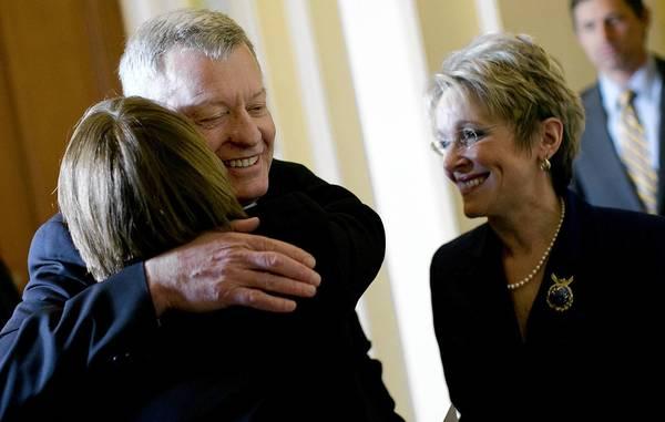Sen. Amy Klobuchar (D-Minn.) hugs Sen. Max Baucus after the Montana Democrat's announcement that he will not seek reelection next year. At right is his wife, Melodee Hanes.
