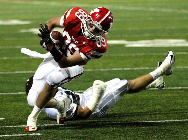 Marist tight end Nic Weishar tries to keep his balance after making a catch against Joliet Catholic on Friday, September 21, 2012.