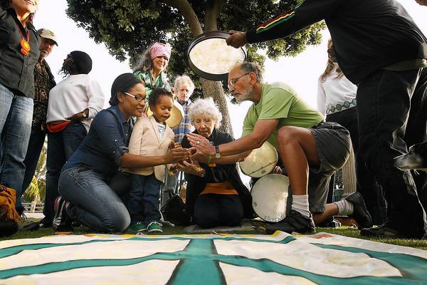 Activist Jerry Rubin, right, with his wife Marissa, along with Shay White, left, and her son Elias Washington, light a candle during a ceremony at the Children's Tree of Life at Santa Monica's Palisades Park in honor of Earth Day.