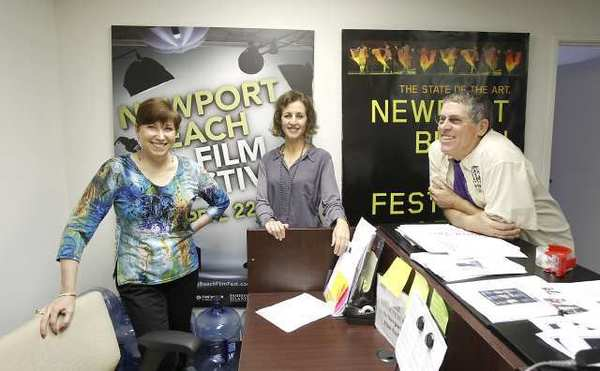 From left, Newport Beach Film Festival volunteers Riki Kucheck, Leslie Feibleman, and Dennis Baker, get ready for this week's film festival in their Newport Beach offices.