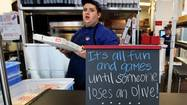 With bright colors, a beverage cooler and staff showing off its pizza-tossing skills, Domino's hopes its customers will think they're in an old-time pizzeria. But they'll probably be taking their dinner home.