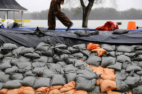 A sandbag levee holds back floodwaters in Clarksville, Mo. Communities along Midwestern waterways monitored and fortified makeshift levees holding back flooding that meteorologists said could worsen or be prolonged by looming storms.