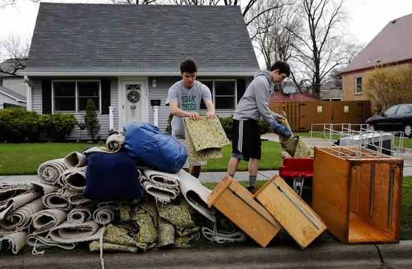 Bobby Mueller, 16, and his friend Nick Fornatto, place wet carpet out in the curb after Mueller's basement was flooded in Elmhurst,
